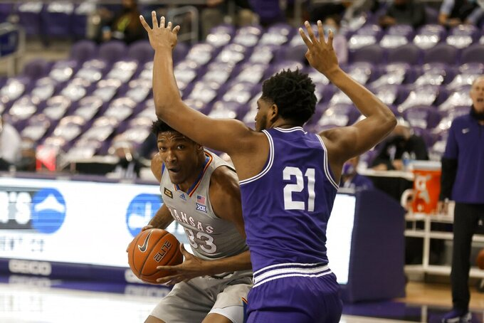 Kansas forward David McCormack (33) works to the basket against TCU center Kevin Samuel (21) in the first half of an NCAA college basketball game in Fort Worth, Texas, Tuesday, Jan. 5, 2021. (AP Photo/Ron Jenkins)