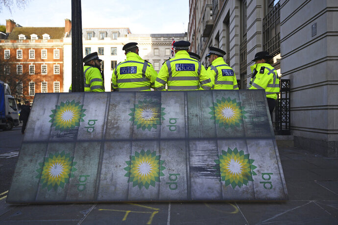 Police officers stand near activists outside BP's headquarters to mark the first day of the oil company's new chief executive Bernard Looney, at St James' Square in London, Wednesday Feb. 5, 2020. Around 100 environmental activists mounted the peaceful protest in central London as Bernard Looney prepared to take up his new role. (Victoria Jones/PA via AP)