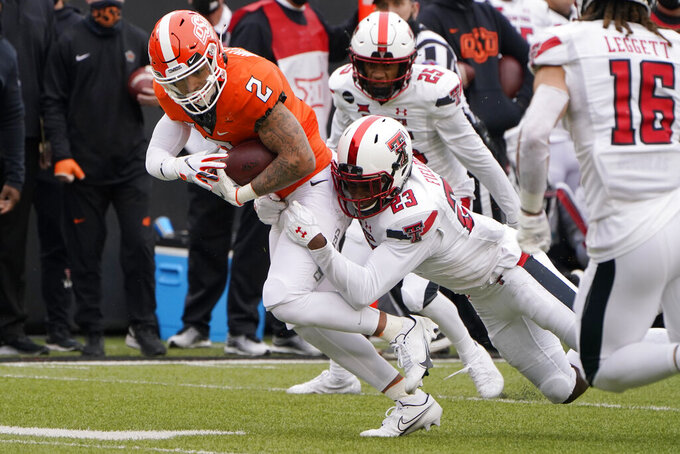 Oklahoma State wide receiver Tylan Wallace (2) is tackled by Texas Tech's DaMarcus Fields (23) in the first half of an NCAA college football game in Stillwater, Okla., Saturday, Nov. 28, 2020. (AP Photo/Sue Ogrocki)