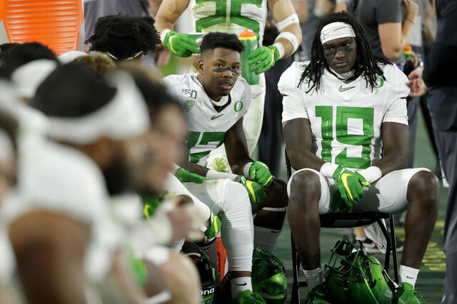 Oregon players sit on the bench during the second half of the team's NCAA college football game against Arizona State, Saturday, Nov. 23, 2019, in Tempe, Ariz. Arizona State won 31-28. (AP Photo/Matt York)