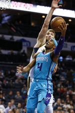 Charlotte Hornets guard Devonte' Graham (4) shoots against Indiana Pacers forward Domantas Sabonis in the first half of an NBA basketball game in Charlotte, N.C., Monday, Jan. 6, 2020. (AP Photo/Nell Redmond)