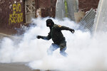 A Bolivian police officer hurls tear gas at backers of former President Evo Morales during clashes, in La Paz, Bolivia, Wednesday, Nov. 13, 2019. Bolivia's new interim president Jeanine Anez faces the challenge of stabilizing the nation and organizing national elections within three months at a time of political disputes that pushed Morales to fly off to self-exile in Mexico after 14 years in power. (AP Photo/Natacha Pisarenko)
