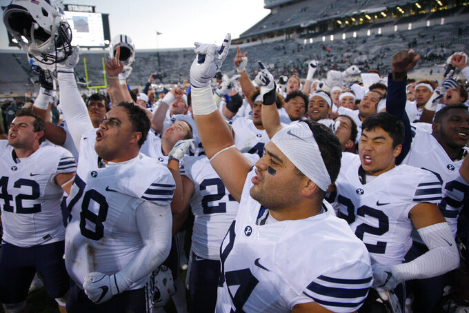 FILE - This Oct. 8, 2016, file photo shows BYU players, including Austin Heder (42), Tuni Kanuch (78), Kesni Tausinga (94) and Hiva Lee, right, celebrate following a 31-14 win over Michigan State in an NCAA college football game, in East Lansing, Mich. A team can go on the road and play a Power Five conference team and earn $1 million-$2 million, often enough to keep other sports programs afloat or fund the training table or academic center. Perhaps no school faces a bigger challenge than independent BYU, which had five games fall off its schedule — Utah, Michigan State, Arizona State and Minnesota to start the season and a Nov. 28 game against Stanford.(AP Photo/Al Goldis)