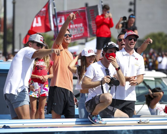 Tampa Bay Buccaneers NFL football quarterback Tom Brady, second from left, gesture as he and others celebrate their Super Bowl 55 victory over the Kansas City Chiefs with a boat parade in Tampa, Fla., Wednesday, Feb. 10, 2021. (Dirk Shadd/Tampa Bay Times via AP)