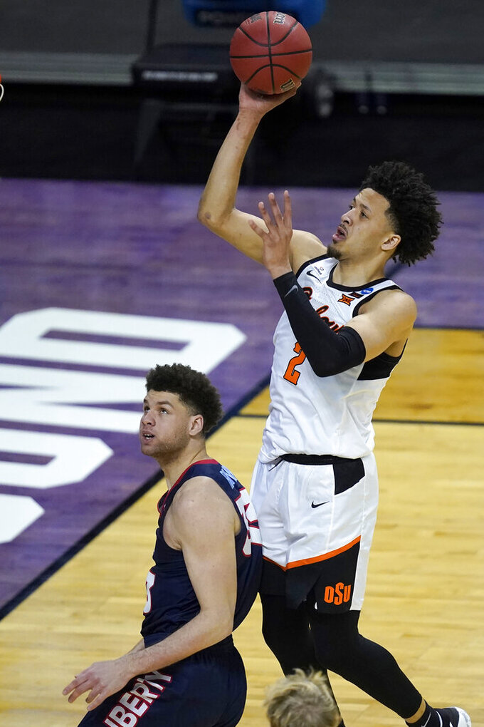 Oklahoma State guard Cade Cunningham (2) shoots over Liberty's Shiloh Robinson during the second half of a first round NCAA college basketball tournament game Friday, March 19, 2021, at the Indiana Farmers Coliseum in Indianapolis.Oklahoma State won 69-60. (AP Photo/Charles Rex Arbogast)