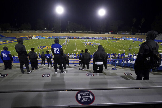 A sign advising social distancing is displayed behind players watching from seats as Air Force kicks off to San Jose State during the first half of an NCAA college football game in San Jose, Calif., Saturday, Oct. 24, 2020. (AP Photo/Jeff Chiu)
