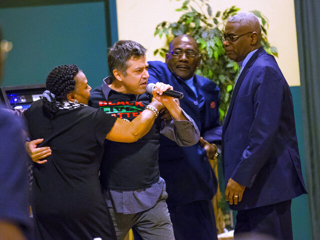 A protester , center, is led out after grabbing the microphone during a gathering of community leaders to discuss Mayor Pete Buttigieg's work Wednesday, Dec. 4, 2019 at the Charles Martin Center in South Bend, Indiana.(Michael Caterina/South Bend Tribune via AP)
