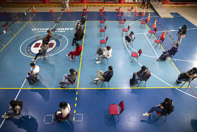 University students wait their turn to be inoculated with the CanSinoCOVID-19 vaccine at a vaccination site vaccinating people over age 23 at Andres Bello University in Santiago, Chile, Thursday, June 3, 2021. (AP Photo/Esteban Felix)