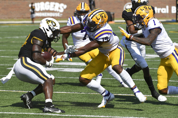 Missouri running back Larry Rountree III, left, runs with the ball as LSU linebacker Jabril Cox (19) and cornerback Eli Ricks (1) defend during the first half of an NCAA college football game Saturday, Oct. 10, 2020, in Columbia, Mo. (AP Photo/L.G. Patterson)
