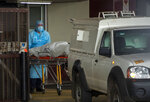 Health workers load a lifeless body into a morgue vehicle at Steve Biko Academic Hospital in Pretoria, South Africa, Monday, Jan. 11, 2021, which is battling an ever-increasing number of Covid-19 patients. (AP Photo/Themba Hadebe)