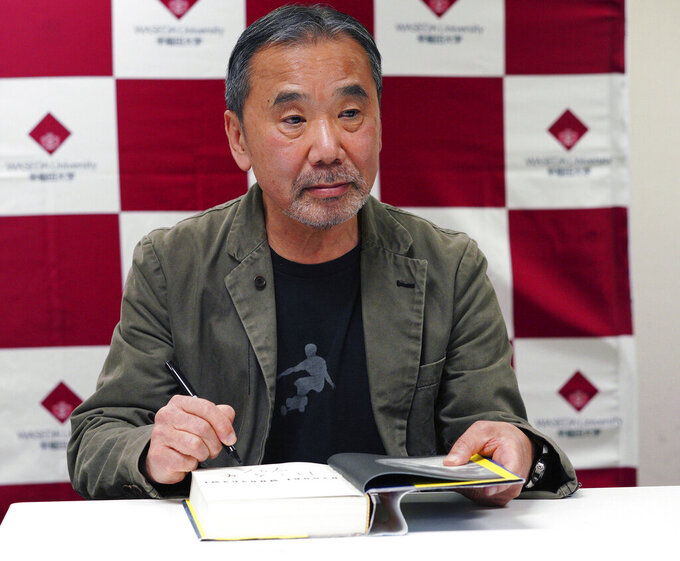 """FILE - In this Nov. 3, 2018, file photo, Japanese novelist Haruki Murakami signs his autograph on his novel """"Killing Commendatore"""" during a press conference in Tokyo. Murakami said politicians need to reduce public uncertainty and fear over the coronavirus by speaking sincerely about the pandemic. Murakami, in a two-hour live New Year's Eve show on Dec. 31, 2020, urged political leaders to """"talk honestly from the gut"""" to the people to encourage them to help slow rising infections which are on the verge of getting out of control. (AP Photo/Eugene Hoshiko, File)"""