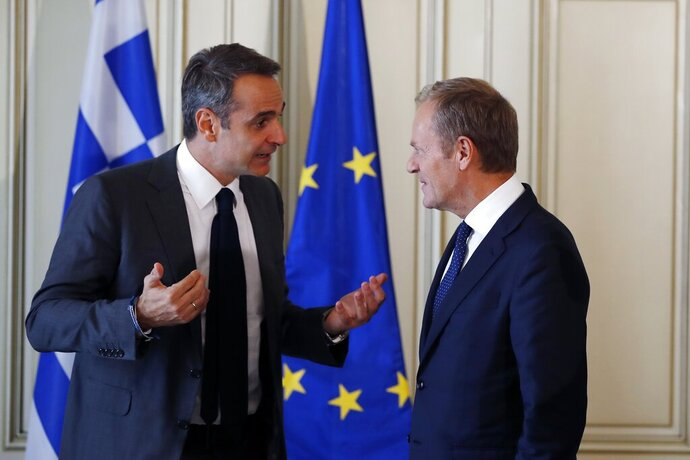 Greece's Prime Minister Kyriakos Mitsotakis, left, speaks with the European Council President Donald Tusk during their meeting at Maximos Mansion in Athens, Wednesday, Oct. 9, 2019. EU leaders have demanded more