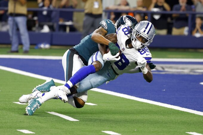 Dallas Cowboys wide receiver CeeDee Lamb (88) is brought down short of the end zone after making a catch by Philadelphia Eagles cornerback Steven Nelson, rear, in the first half of an NFL football game in Arlington, Texas, Monday, Sept. 27, 2021. (AP Photo/Ron Jenkins)