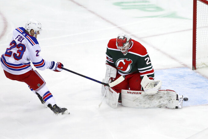 New York Rangers defenseman Adam Fox (23) beats New Jersey Devils goaltender Mackenzie Blackwood (29) to score a goal during the first period of an NHL hockey game in Newark N.J., on Saturday, March 6, 2021. (Andrew Mills/NJ Advance Media via AP)