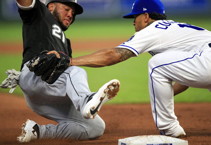 Kansas City Royals third baseman Cheslor Cuthbert, right, tags out Chicago White Sox's Welington Castillo (21) during the fifth inning of a baseball game at Kauffman Stadium in Kansas City, Mo., Wednesday, July 17, 2019.  (AP Photo/Orlin Wagner)