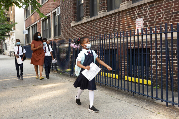 A girl leads her mother and brothers as they arrive at Brooklyn's PS 245, Monday, Sept. 13, 2021, in New York. Classroom doors are swinging open for about a million New York City public school students in the nation's largest experiment of in-person learning during the coronavirus pandemic. (AP Photo/Mark Lennihan)
