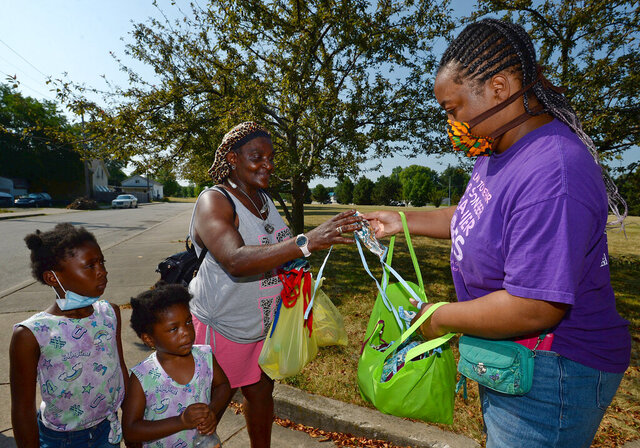 Monique Jones, left, of Erie, receives a face mask Friday, July 10, 2020 from Rajahnee Hollamon, a member of the Blue Coats, in the 900 block of East Eighth Street in Erie, Pa. A group of volunteers was canvassing the neighborhood to educate residents about COVID-19. (Jack Hanrahan/Erie Times-News via AP)