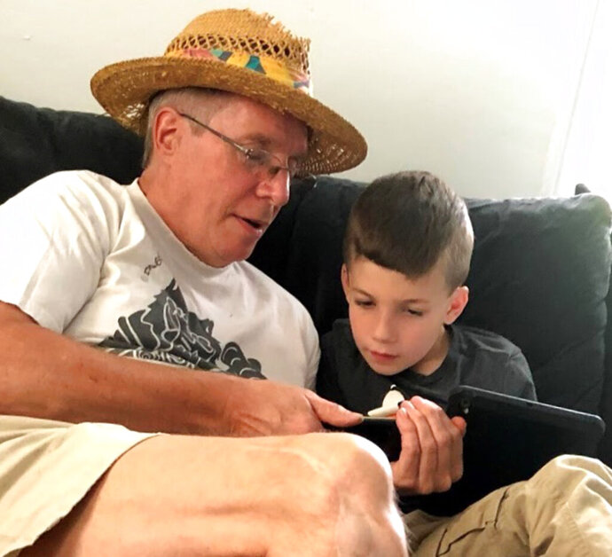 This summer 2018 photo provided by Al Mattin on Friday, May 10, 2019 shows his father, Stephen, and son, Ronan, at Stephen's home in Kensington, N.H. The Handel & Haydn Society had just finished a rendition of Mozart's