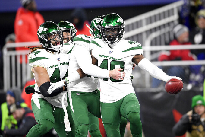New York Jets players celebrate after linebacker B.J. Bello, right, returned a Baltimore Ravens blocked punt for a touchdown during the second half of an NFL football game, Thursday, Dec. 12, 2019, in Baltimore. (AP Photo/Nick Wass)