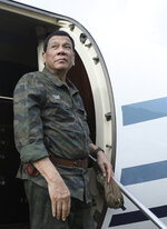 In this July 15, 2019, photo released by the Malacanang Presidential Photo, Philippine President Rodrigo Duterte arrives at the Jolo airport, Sulu province, southern Philippines. Duterte is