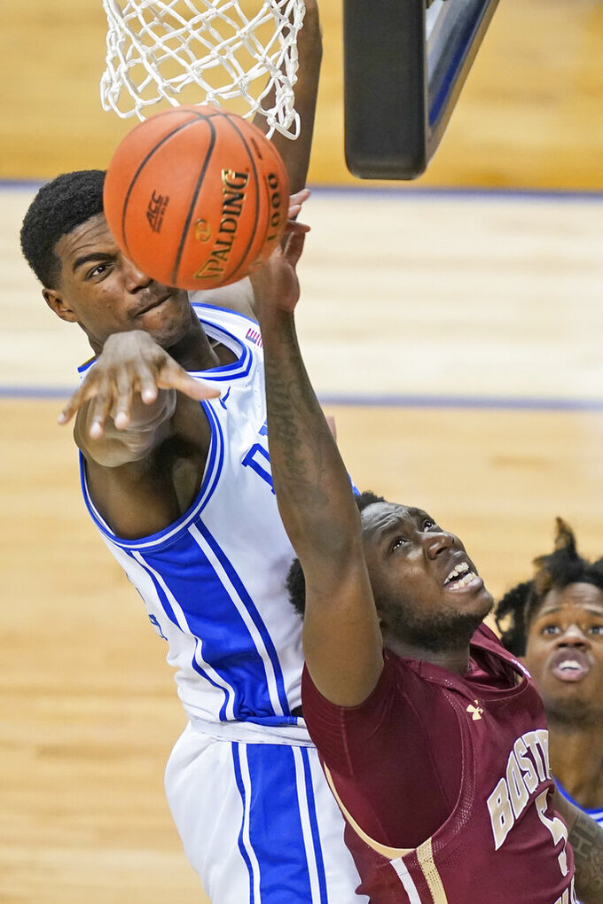 Duke forward Henry Coleman III, left, blocks the shot of Boston guard Jay Heath (5) during the second half of an NCAA college basketball game in the first round of the Atlantic Coast Conference tournament in Greensboro, N.C., Tuesday, March 9, 2021. (AP Photo/Gerry Broome)