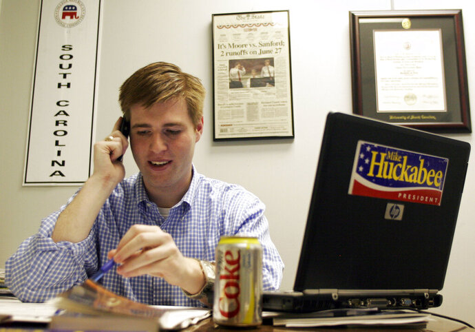FILE - In this Dec. 28, 2007, file photo, Adam Piper, one of only four full-time staffers for Mike Huckabee's presidential campaign in South Carolina, answers calls and returns emails from the state campaign headquarters in Columbia, S.C. Piper, the executive director of a national group that advocates for Republican attorneys general has resigned in the fallout of a robocall sent out by the association's political arm urging people to march to the U.S. Capitol last week ahead of the violent assault that followed. The Republican Attorneys General Association and the Rule of Law Defense Fund accepted the voluntary resignation of Piper on Monday, Jan. 11, 2021. (AP Photo/Brett Flashnick, File)