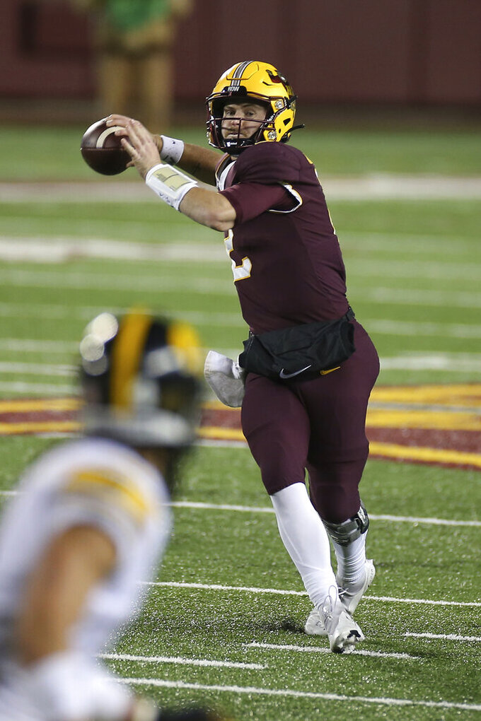Minnesota quarterback Tanner Morgan looks for a receiver during the second half of the team's NCAA college football game against Iowa on Friday, Nov. 13, 2020, in Minneapolis. Iowa won 35-7. (AP Photo/Stacy Bengs)