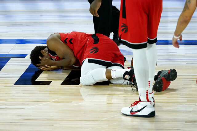 Toronto Raptors' Kyle Lowry lies on the court after being hit in the face during the second half of an NBA basketball game against the Miami Heat Monday, Aug. 3, 2020, in Lake Buena Vista, Fla. (AP Photo/Ashley Landis, Pool)