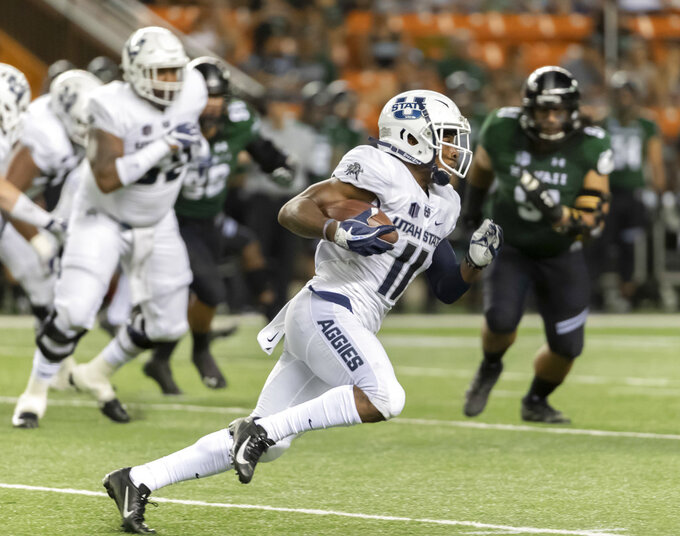 Utah State wide receiver Aaren Vaughns (11) runs with the football in the first half of an NCAA college football game against Hawaii, Saturday, Nov. 3, 2018, in Honolulu. (AP Photo/Eugene Tanner)