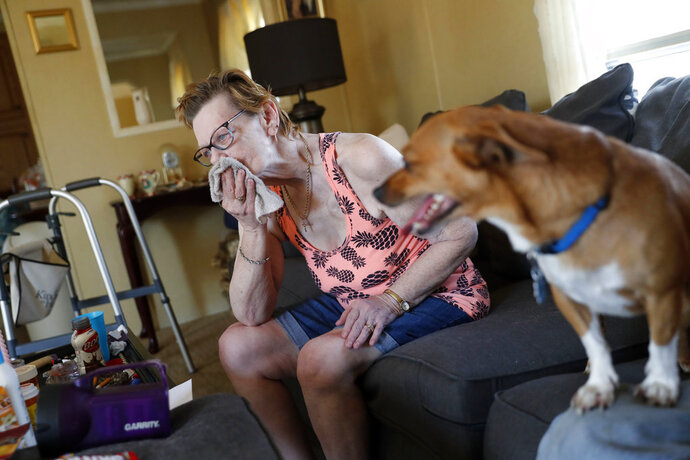 Sandra Sheffield, 72, uses a washcloth to wipe sweat from her face, in her home, which now has no electricity, in the aftermath of Hurricane Michael in Panama City, Fla., Wednesday, Oct. 17, 2018. She and her husband refuse to leave their home, and neighbors are trying to assist them with fans and a generator. (AP Photo/Gerald Herbert)
