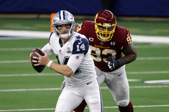 Dallas Cowboys quarterback Andy Dalton (14) scrambles out of the pocket under pressure from Washington Football Team defensive tackle Jonathan Allen (93) during the first half of an NFL football game in Arlington, Texas, Thursday, Nov. 26, 2020. (AP Photo/Ron Jenkins)