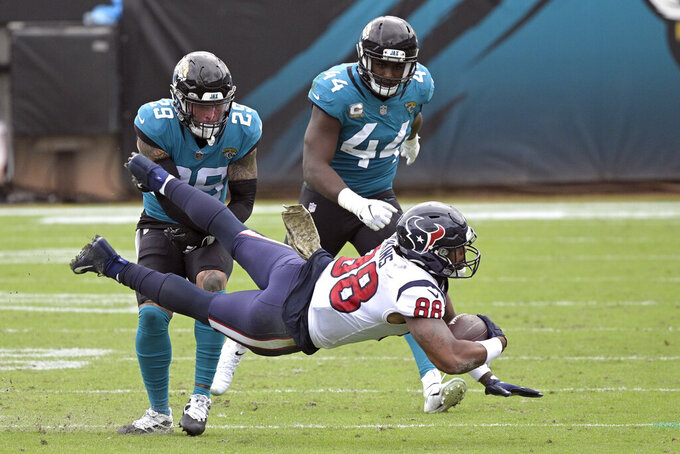Houston Texans tight end Jordan Akins (88) is tackled by Jacksonville Jaguars safety Josh Jones (29) and linebacker Myles Jack (44) after a reception during the first half of an NFL football game, Sunday, Nov. 8, 2020, in Jacksonville, Fla. (AP Photo/Phelan M. Ebenhack)