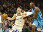 Milwaukee Bucks' Donte DiVincenzo drives past Charlotte Hornets' Bismack Biyombo during the second half of an NBA basketball game Saturday, Nov. 30, 2019, in Milwaukee. (AP Photo/Jeffrey Phelps)