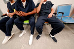 Detainees sit and wait for their turn at the medical clinic at the Winn Correctional Center in Winnfield, La., Thursday, Sept. 26, 2019. Since 2018, eight Louisiana jails have started detaining asylum seekers, making Louisiana an unlikely epicenter for immigrant detention under President Donald Trump. (AP Photo/Gerald Herbert)