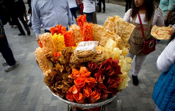 FILE - In this July 5, 2016 file photo, a street vendor sells fried snack food in Mexico City. As more states propose or approve bans on junk food sales to minors, Mexico is seeing the tide turn against high-calorie snacks that experts say have given the country one of the highest rates of childhood obesity and an unusually young coronavirus death toll.   (AP Photo/Eduardo Verdugo, File)