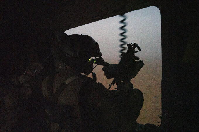 FILE- In this Monday June 7, 2021 file photo, a French Barkhane force soldiers mans a machine gun on board a Caiman transport helicopter during a night mission in Gao, Mali. As France prepares to scale back its military presence in Africa, its soldiers are again confronting the very threats that brought the army here in the first place. In northern Mali, some villages in the north are again falling under the control of Islamic extremists who want to impose strict Islamic law. Last month, French President Emmanuel Macron announced the official end of Barkhane, France's seven-year operation fighting extremists linked to al-Qaida and the Islamic State in Africa's Sahel region. (AP Photo/Jerome Delay, File)