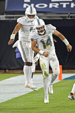 Miami Dolphins quarterback Ryan Fitzpatrick (14) celebrates after throwing a touchdown pass against the Jacksonville Jaguars with teammate quarterback Tua Tagovailoa, left, during the first half of an NFL football game, Thursday, Sept. 24, 2020, in Jacksonville, Fla. (AP Photo/Phelan M. Ebenhack)