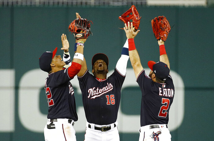FILE - In this June 4, 2019, file photo, Washington Nationals outfielders Juan Soto, from left, Victor Robles and Adam Eaton celebrate after beating the Chicago White Sox 9-5 in an interleague baseball game in Washington. For the 2019 Nationals, Game No. 60 on June 4, 2019, served as something of a microcosm of the whole season and an example of their