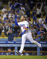Los Angeles Dodgers' Max Muncy tosses his helmet before scoring after hitting a game-winning home run during the 10th inning of the team's baseball game against the Toronto Blue Jays on Wednesday, Aug. 21, 2019, in Los Angeles. The Dodgers won 2-1. (AP Photo/Mark J. Terrill)