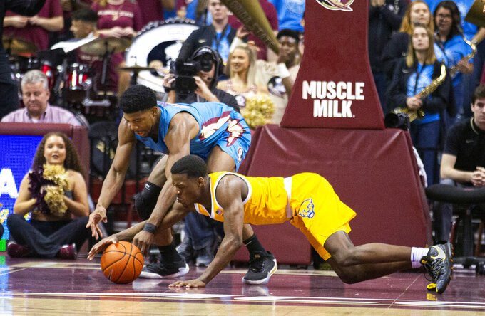 Florida State forward Malik Osborne, top, and Pittsburgh guard Xavier Johnson (1) scramble for the ball during the first half of an NCAA college basketball game in Tallahassee, Fla., Tuesday, Feb. 18, 2020. (AP Photo/Mark Wallheiser)