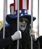 An actor impersonates the United States imprisoned in a cage in the anti-U.S. annual rally in front of the former U.S. Embassy in Tehran, Iran, Monday, Nov. 4, 2019. Reviving decades-old cries of