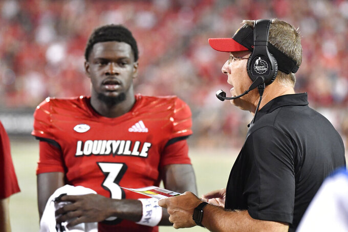 Louisville head coach Scott Satterield, right, talks with quarterback Malik Cunningham (3) during the second half of an NCAA college football game against Central Florida in Louisville, Ky., Friday, Sept. 17, 2021. (AP Photo/Timothy D. Easley)