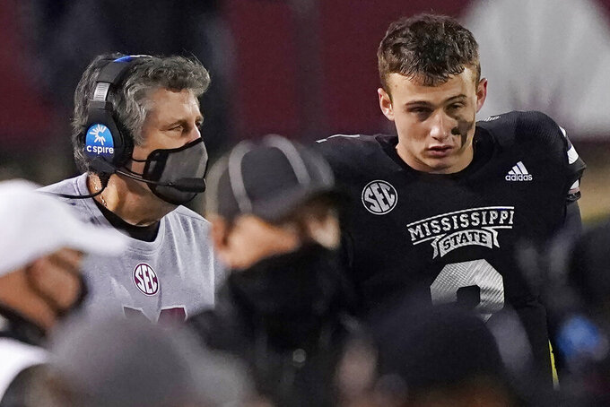 Mississippi State head coach Mike Leach, left, speaks with quarterback Will Rogers (2) in the second half of an NCAA college football game against Missouri, Saturday, Dec. 19, 2019, in Starkville, Miss. (AP Photo/Rogelio V. Solis)