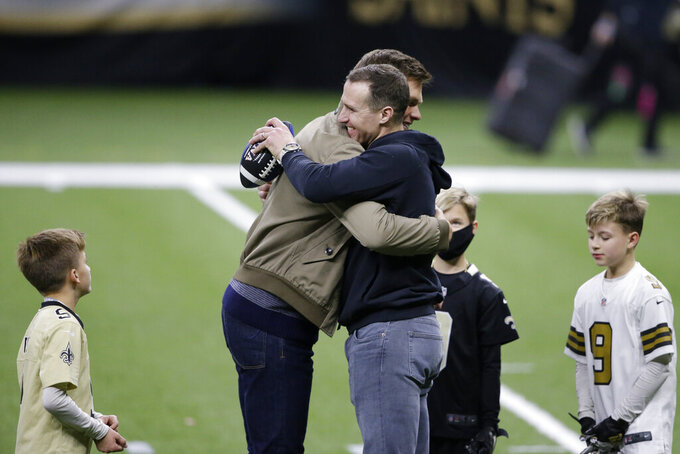 New Orleans Saints quarterback Drew Brees right, embraces Tampa Bay Buccaneers quarterback Tom Brady as Bree's children look on after an NFL divisional round playoff football game between the New Orleans Saints and the Tampa Bay Buccaneers, Sunday, Jan. 17, 2021, in New Orleans. The Tampa Bay Buccaneers won 30-20. (AP Photo/Butch Dill)