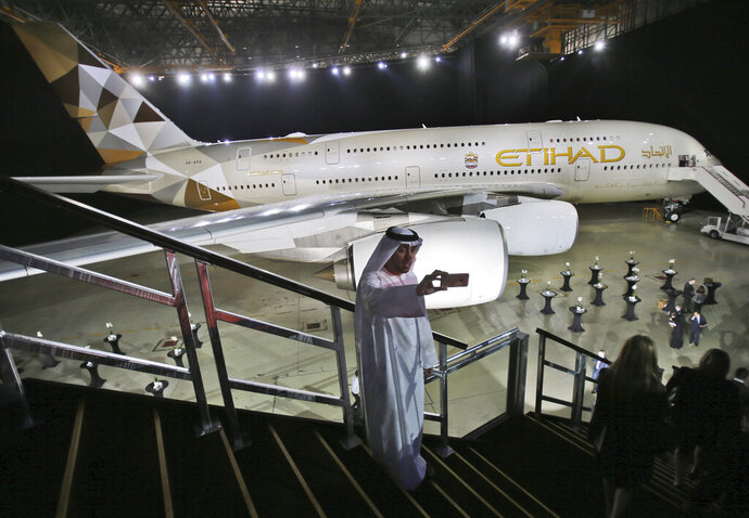FILE - In this Dec. 18, 2014 file photo, an Emirati man takes a selfie in front of a new Etihad Airways A380 in Abu Dhabi, United Arab Emirates. Abu Dhabi-based Etihad Airways said Thursday, Aug. 6, 2020, that its core operating losses amounted to $758 million for the first half of the year, driven by a nearly 40% drop in revenue due in part to the impact of the coronavirus pandemic. (AP Photo/Kamran Jebreili, File)