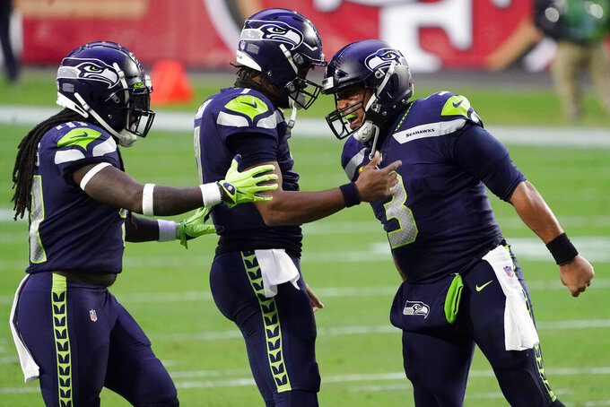Seattle Seahawks quarterback Russell Wilson (3) celebrates after a touchdown against the San Francisco 49ers with quarterback Geno Smith and linebacker Ray-Ray Armstrong, left, during the second half of an NFL football game, Sunday, Jan. 3, 2021, in Glendale, Ariz. (AP Photo/Rick Scuteri)