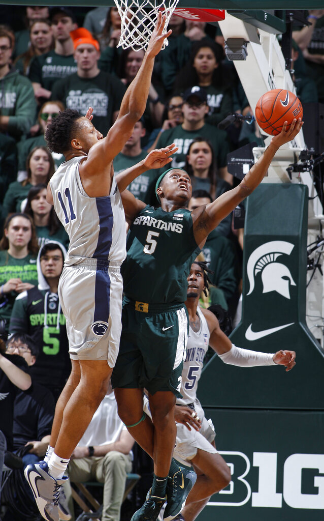 Michigan State's Cassius Winston, right, shoots next to Penn State's Lamar Stevens during the first half of an NCAA college basketball game Tuesday, Feb. 4, 2020, in East Lansing, Mich. (AP Photo/Al Goldis)