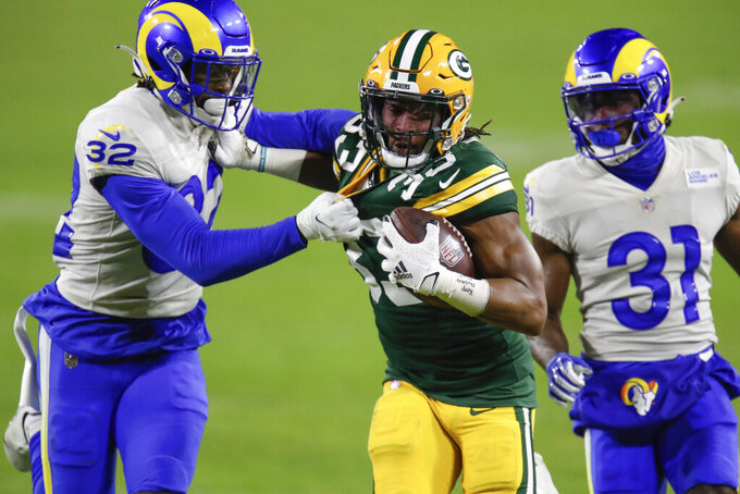 Green Bay Packers' Aaron Jones (33) is chased down by Los Angeles Rams' Jordan Fuller (32) and Rams' Darious Williams during the second half of an NFL divisional playoff football game Saturday, Jan. 16, 2021, in Green Bay, Wis. (AP Photo/Matt Ludtke)