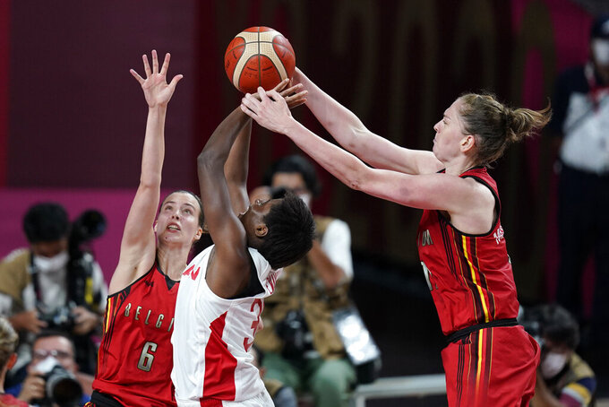 Japan's Evelyn Mawuli, center, shoots between Belgium's Antonia Delaere, left, and Emma Meesseman, right, during a women's basketball quarterfinal round game at the 2020 Summer Olympics, Wednesday, Aug. 4, 2021, in Saitama, Japan. (AP Photo/Charlie Neibergall)