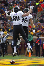 Northwestern running back Isaiah Bowser (25) celebrates with teammate wide receiver Trey Pugh after Bowser scored a touchdown against Minnesota during an NCAA college football game Saturday, Nov. 17, 2018, in Minneapolis. (AP Photo/Stacy Bengs)